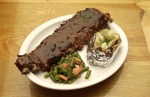 Uncle Ed's Catering, Genoa City — FULL RACK OF TANGY BABY BACK RIBS TOPPED WITH UNCLE ED'S BACKYARD BBQ SAUCE AND MARINADE, SERVED WITH BAKED POTATO AND GREEN BEAN AND TOMATO SAUTE.