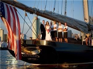 "Yacht ""America"", San Diego — Bride & Groom pose with the yacht crew on the stern of the famous yacht ""America"", her lovely Gold Eagle glistening in the sunset and American flag flying proudly off the boom."
