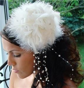 Fairytale Bridal Tiara, Miami — This vintage-inspired bridal hat is an enchanting alternative to a bridal veil. The piece features a feather base with a bow and three fabric roses on top. Faux pearls and rhinestones subtly sit at the center of the roses, and a spray of faux pearls dangle beautifully off of one side.