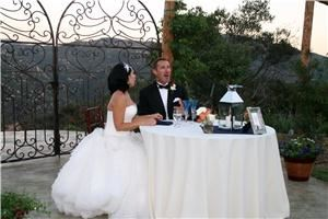 Secluded Garden Estate, Pala — SWEETHEART TABLE FOR BRIDE AND GROOM WITH STUNNING PICTURESQUE VIEW AND SWEETHEART GATE BEHIND THEM.