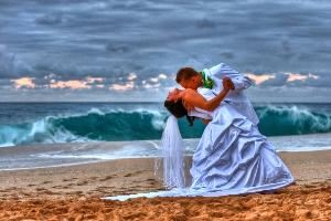 Phillips Photography, Waipahu — A groom dips his new bride as a North Shore wave crashes in the background.