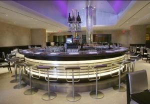 The Champagne And Caviar Bar, N9NE Steak House - Las Vegas, Las Vegas — N9NE Steakhouse is anything but one of those hushed environments in which buttoned-down businessmen tuck into their T-bones. The traditional red leather, brass and mahogany have been traded in for a more contemporary look that appeals to a hip, diverse crowd. Upon entering the dramatic 12,500 square foot restaurant, wide-eyed patrons are greeted by a two-sided wall of water and stunning glass-ensconced wine cellar. Limestone walls, mirrored mosaics and ultra-suede booths are among elegant appointments bathed in soft illumination. In the center of the room--beneath a silver-leaf domed ceiling shimmering under a 300-color intelligent lighting system--is N9NE Steakhouse's trademark circular Champagne and Caviar Bar. In addition to providing a fun, communal dining experience for solos or groups, the bar serves as a focal point that generates energy throughout the dining room.