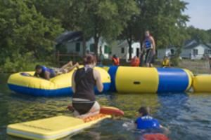 Waterfront, Camp Scully, Wynantskill — Our beach borders Snyder's Lake. A giant water trampoline and launcher is very popular. Sailing, kayaking and canoeing are available from our dock. Beach parties and BBQ's can be held.
