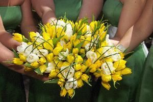 "Little Black Dress Brigade, Little Rock — Just a sample of the many bridesmaid bouquets we've created.  This one uses white and yellow tulips and sassy strips of bear grass.  The bride gave each girl a ""lucky clover"" pin to top off the Irish theme of the event and we pinned the clover onto the hand tied chocolate brown ribbon."