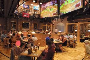 Main Dining Room, NBA City, Orlando — The main dining room featuring NBA and WNBA black and white photography and a floor-to-ceiling basketball mural. Two 10 x 15 foot video screens display exclusive NBA City programming, highlighting the greatest moments in the NBA and WNBA and showcasing the hottest new stars of tomorrow. From Bill Russell and Wilt Chamberlain to Kevin Garnett and Kobe Bryant, the greatest moments, performances and rivalries of the NBA come to life at NBA City.